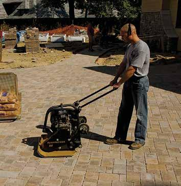 Figure 9. Compacting the pavers and bedding sand. Figure 10. Spreading and sweeping joint sand.