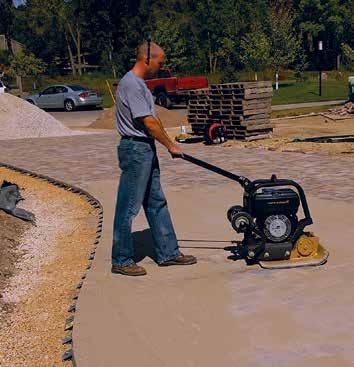 Figure 11. Vibrating sand into the joints. the pavement. Pavers are cut with a double bladed splitter or a masonry saw. See Figure 8. A saw gives a smooth cut. Gaps greater than 3 /8 in.