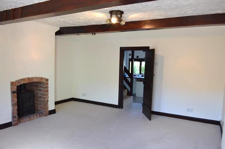 aspect, feature stone, recessed fireplace and hearth housing a cast iron gas fired log burner, single panelled radiator. Telephone point.