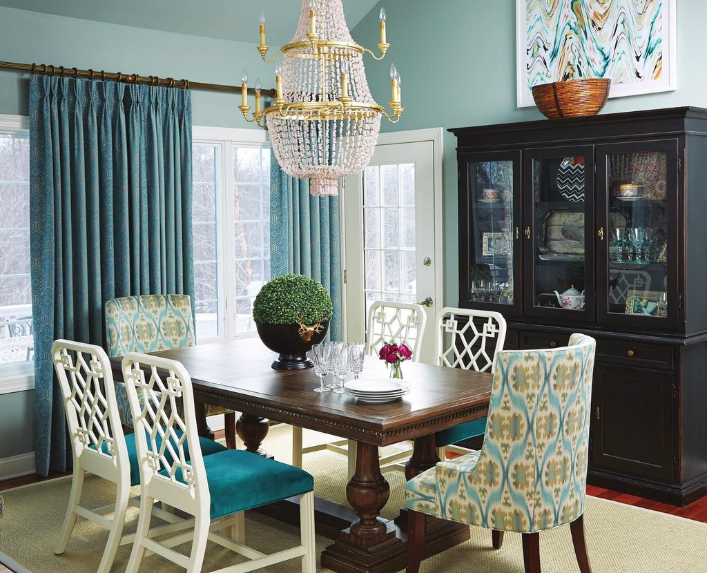 ample light via the skylights. Turquoise fabric on the chairs gives the room a jolt of color, and an unusual chandelier draws the eye up.