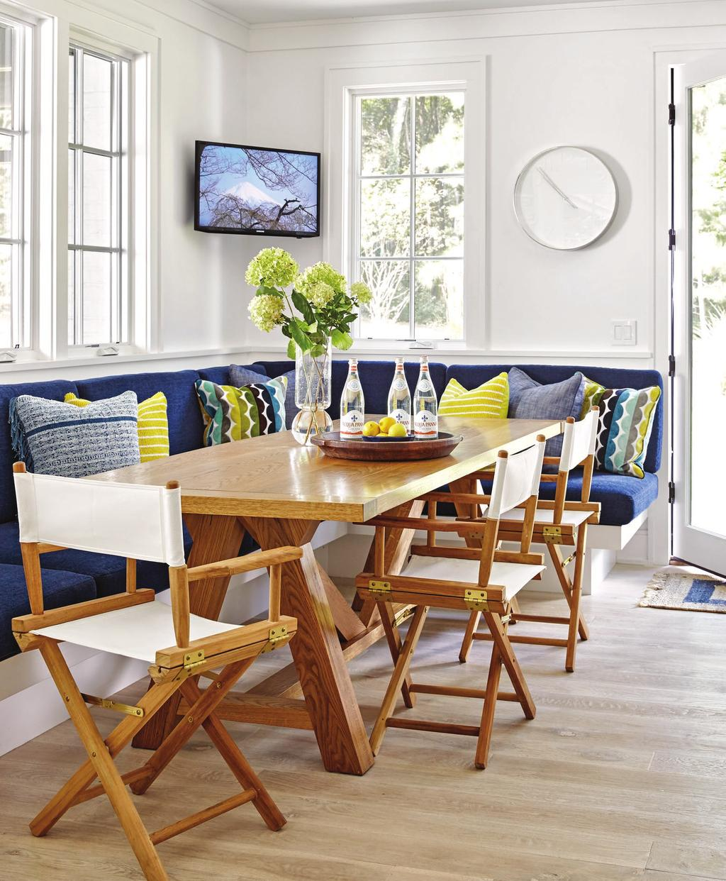 The banquette cushions wear soft but durable chenille; pillows in outdoor fabrics punch up the navy with citrusy hues.