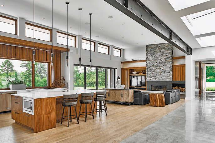 Antiqued exposed beams run the length of the house and book-matched walnut walls and locallysourced ledgestone soften the angular modern elements.