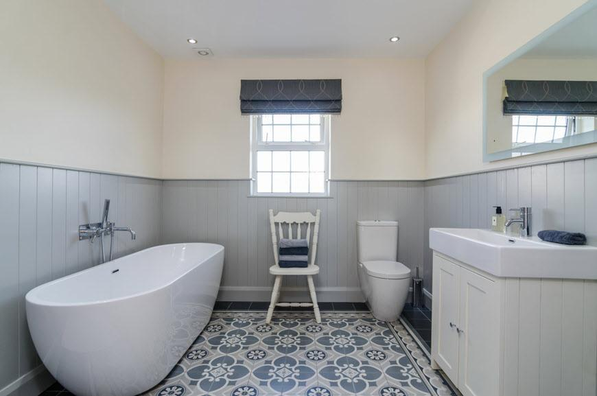 BATHROOM: White suite comprising free standing bath with mixer tap and shower attachment, low