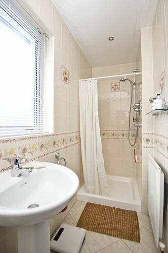 24m) ENSUITE SHOWER ROOM: Comprising tiled shower with chrome fittings, low flush wc, pedestal wash