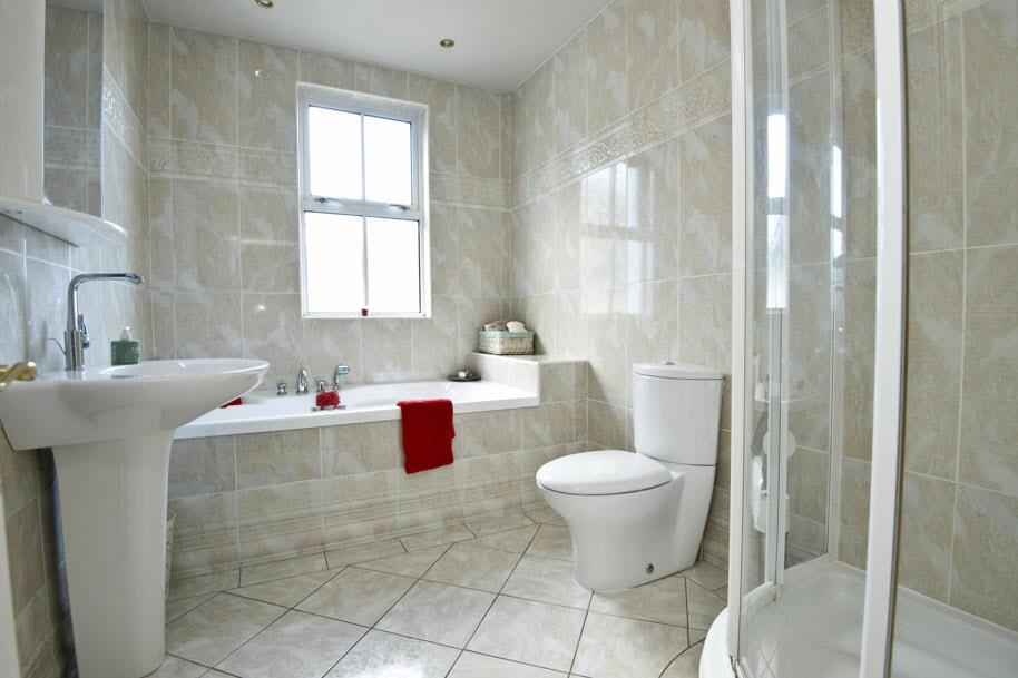 BATHROOM: Modern white suite comprising Jacuzzi bath with retractable shower.
