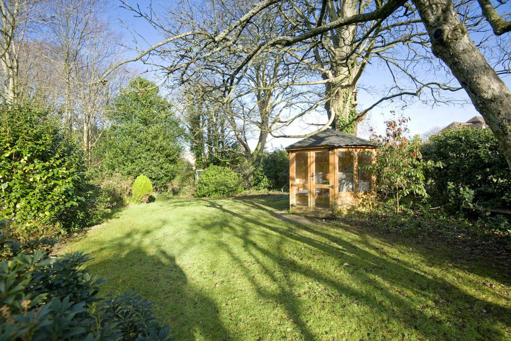 FRONT GARDEN: Lawn with well-stocked beds featuring superb variety of mature plants, trees