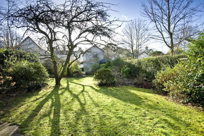 REAR GARDEN: Extensive lawns, abundance of plants, trees and flowering shrubs.