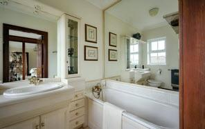 BATHROOM: White bathroom suite comprising panelled bath, fully tiled built-in shower