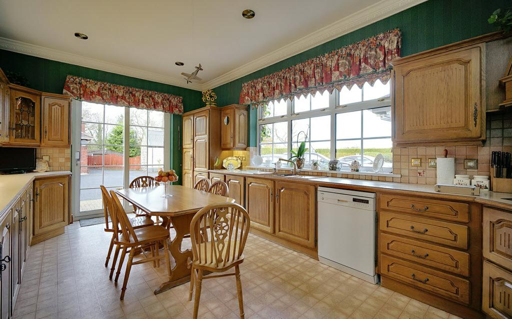5m) Solid oak fitted kitchen with excellent range of high and low level units with leaded glazed display cabinets, laminate worktops with oak