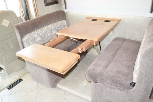 Align table extension pegs with table insert holes and push edge of dinette table in