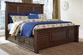 side drawer storage Rolled top tufted upholstered bed has a light brown textured fabric and nail head trim Dovetailed drawers are fully finished and use metal