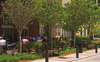 This landscape provides a comfortable, safe, and aesthetically pleasing pedestrian environment. A railing separates the outdoor dining area from the busy street.