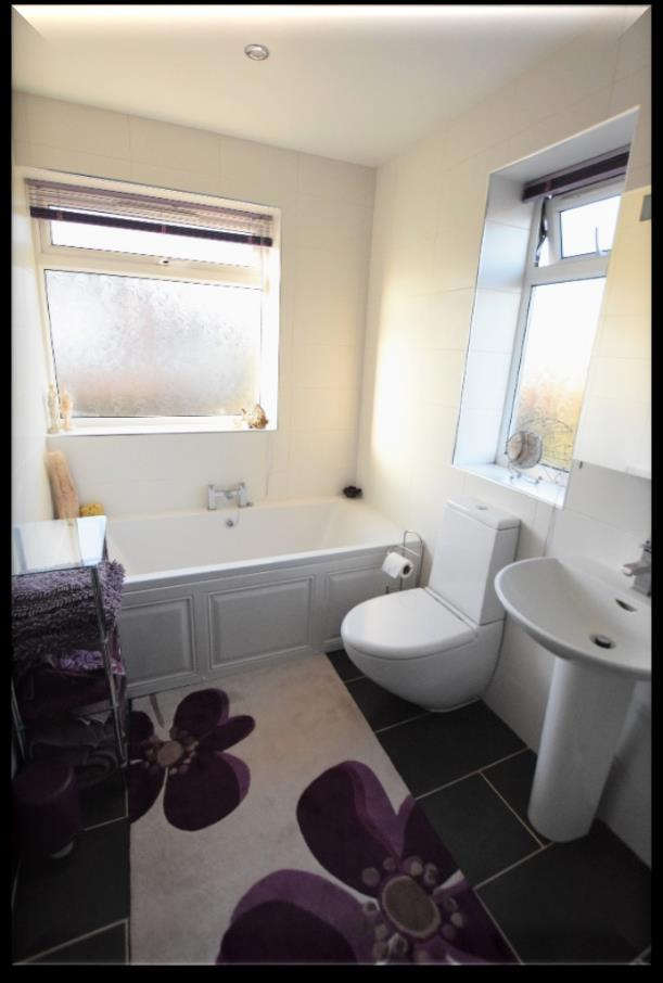 tiled floor, feature heated towel warmer/radiator, inset LED spotlights, extractor, two upvc double glazed windows with frosted glass having fitted blinds