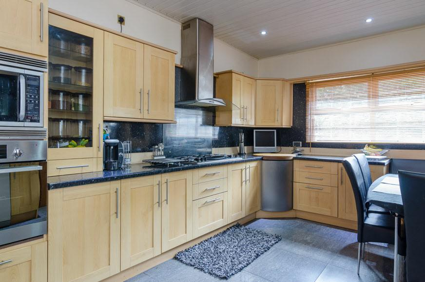 66m) Extensive range of high and low level units, work surfaces with tiled panelled splash back, 1 1/2 basin sink unit with mixer tap, glass display cabinets,