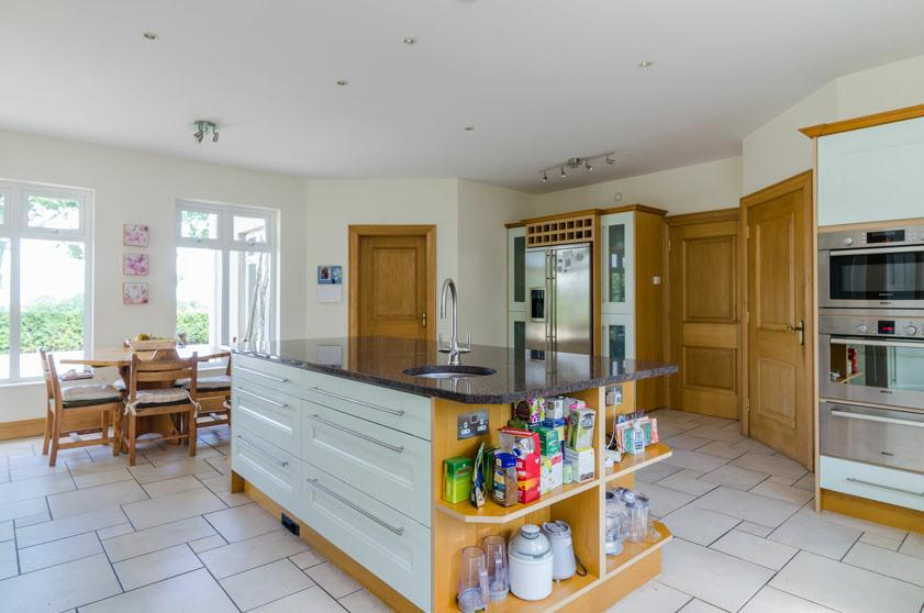 display cabinets, housing for American fridge freezer, cooker range with 6 ring gas hob and multi ovens with splash back and ornamental surround.