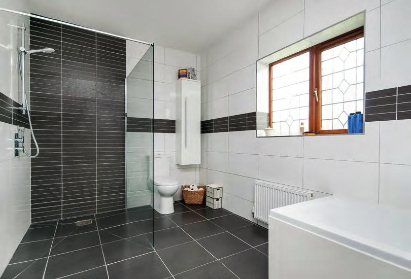 EN-SUITE SHOWER ROOM: Fully ceramic tiled to floor and walls, corner shower cubicle with jet system, concealed cistern w.