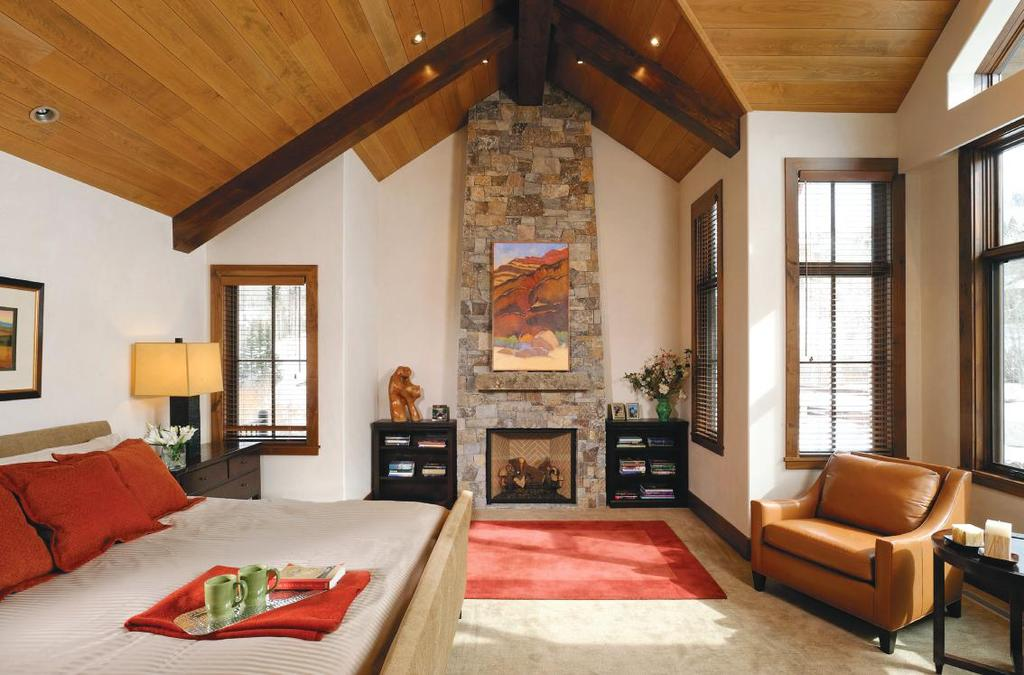 ABOVE: Red and orange jewel tones provide the rich accent hues of this master retreat. The fireplace mirrors the same stone, as well as identical wood beams from the great room.