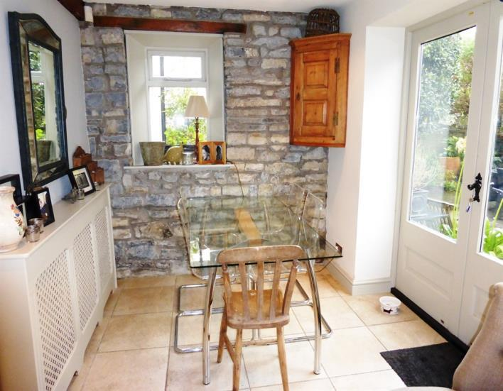 The dining area has an exposed stone wall at one end as well as a double glazed window and double glazed French doors to the rear garden. Tiled floor. Inset lights to the ceiling.