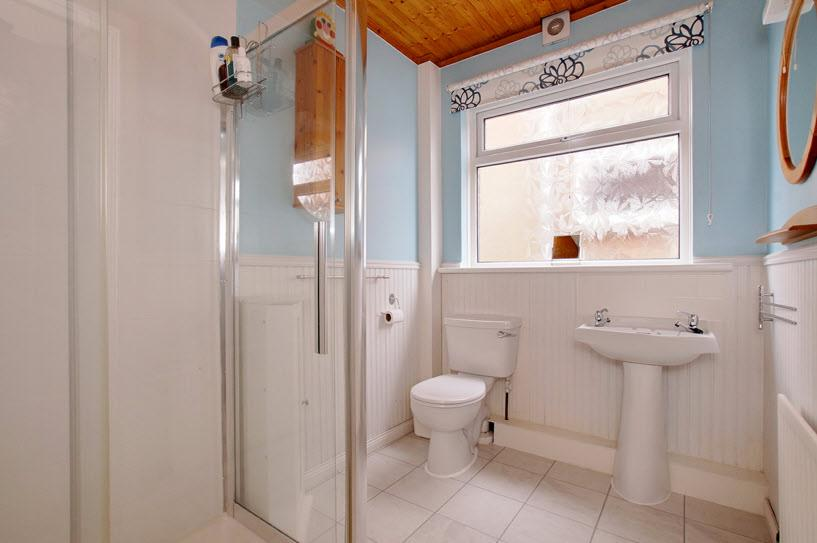 SHOWER ROOM: Fully tiled, double shower cubicle, Triton electric shower, low flush WC, pedestal