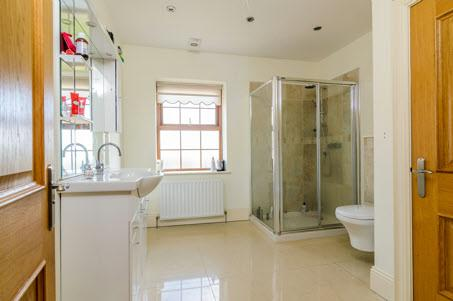 ENSUITE SHOWER ROOM: White suite comprising vanity unit with built-in mirror and