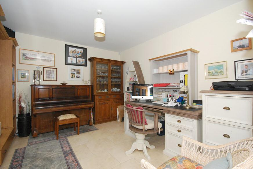 "STUDY: 13' 3"" x 11' 6"" (4.04m x 3.51m) Ceramic tiled floor, fitted bookcases with storage drawer and window pelmet with low voltage lighting, half glazed door from hall."
