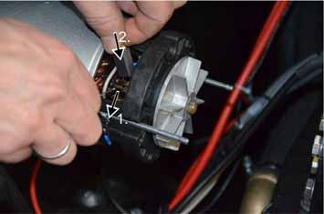 Pull back the retaining spring. Insert new carbon block and push it in. Electrically connect the carbon block.