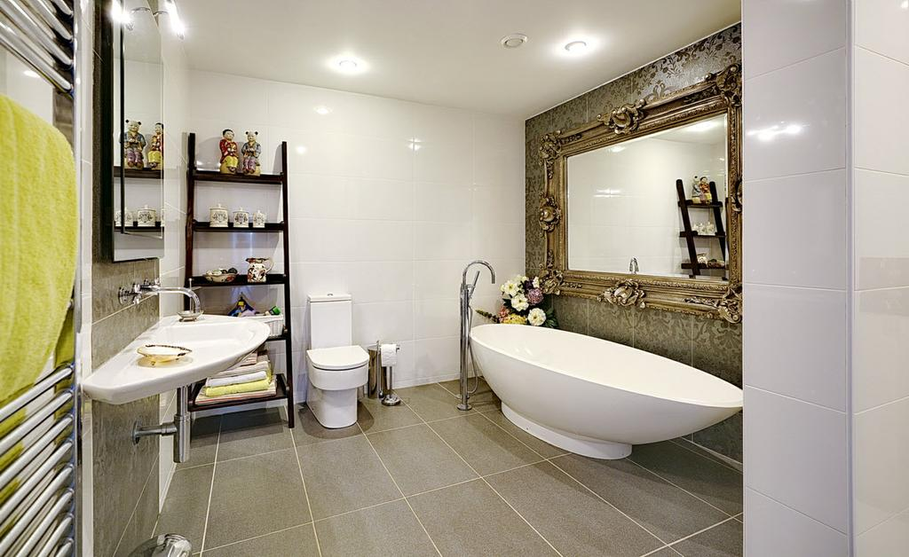 LUXURY BATHROOM: Oval free standing bath with mixer tap and telephone hand shower, contemporary wash hand basin with mixer tap, low flush wc, walk-in shower with thermostatic shower unit and rain